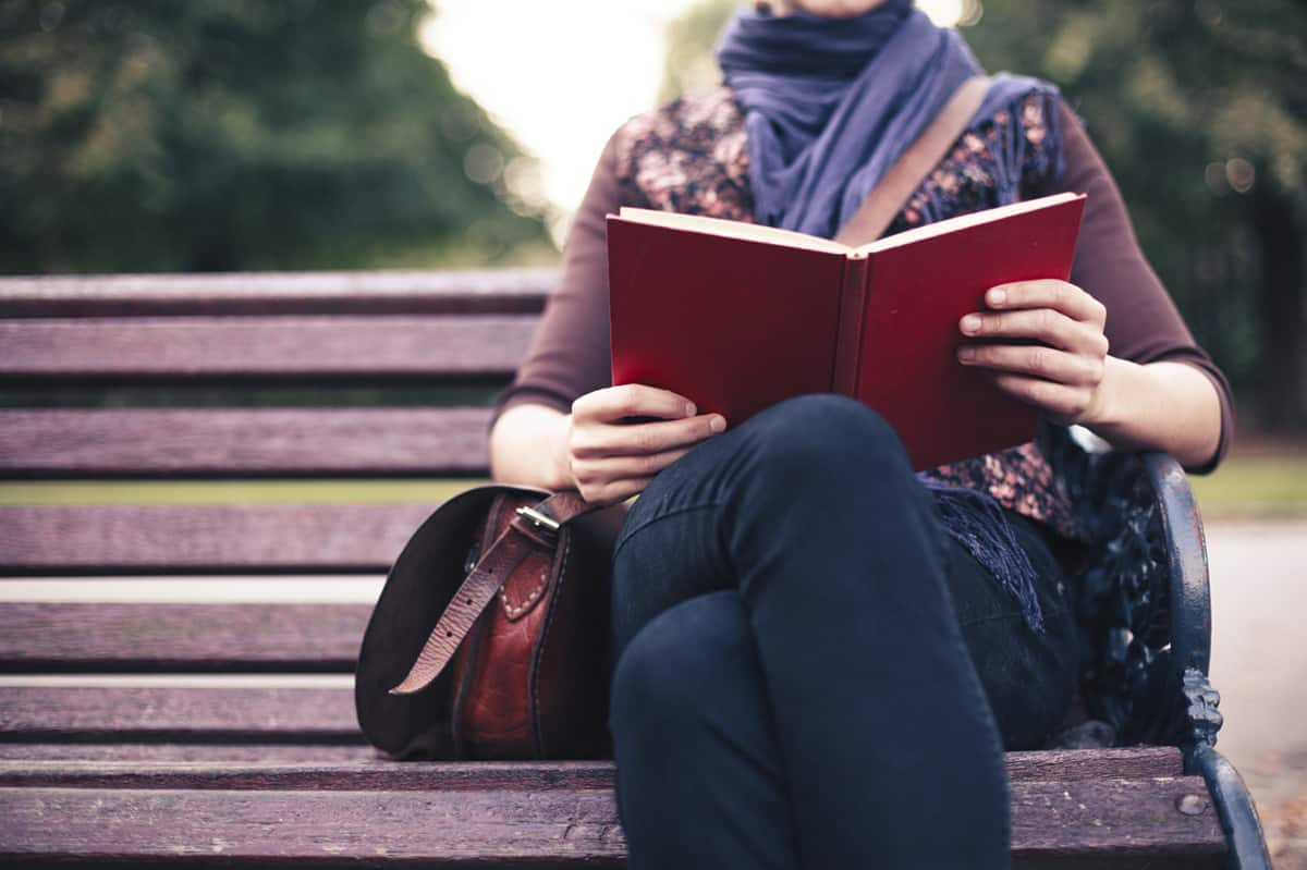 Young-woman-reading-on-park-bench-000061499278_sm