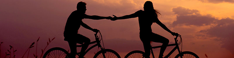 People biking and holding hands