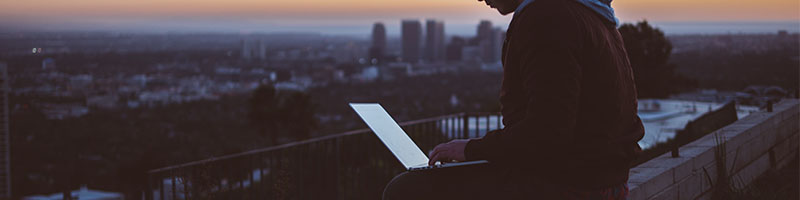 A man using a laptop overlooking the city